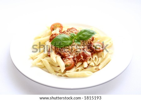 A plate of penne pasta with tomato sauce and a sprinkling of cheese with sliced cherry tomatoes and a sprig of basil with copy space