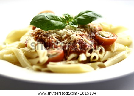 A plate of penne pasta with tomato sauce and a sprinkling of cheese with sliced cherry tomatoes and a sprig of basil with copy space - stock photo