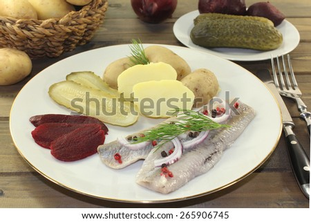 a plate of pickled herring fillet, boiled potatoes, beetroot and pickled gherkins - stock photo