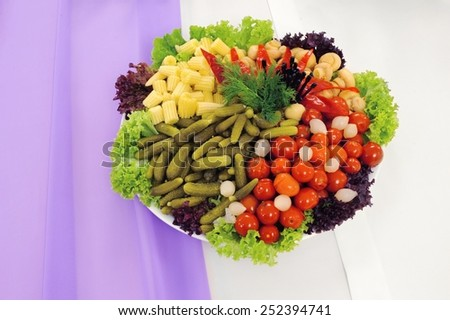 a plate of pickled vegetables cucumber tomato corn - stock photo