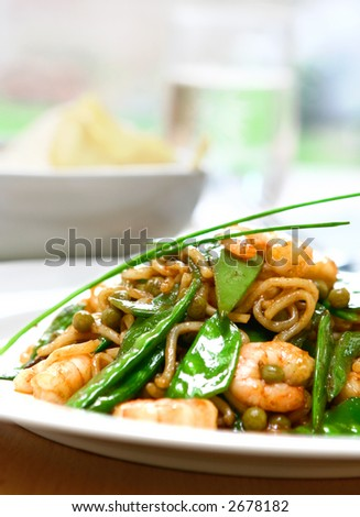 A plate of prawn stir fry noodles with beans and peas garnish with chives served on white plate. - stock photo