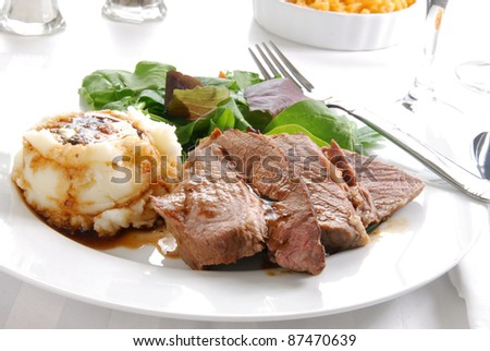 A plate of roast beef and mashed potatoes with a side of macaroni and cheese - stock photo