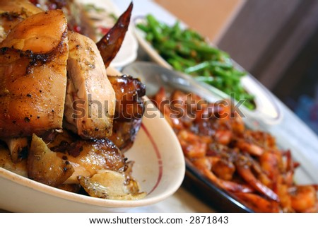 A plate of roasted chicken spread on the dinner table with prawns and vegetables in the background.