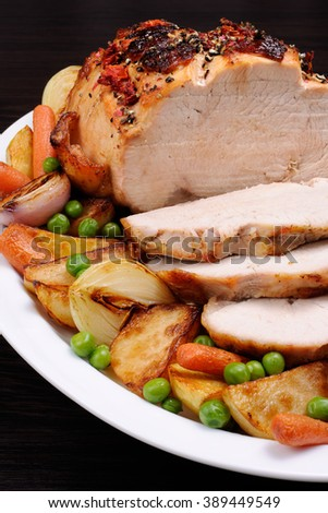 A plate of roasted turkey breast slices with vegetables - stock photo