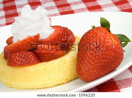 A plate of shortcake, topped with fresh strawberry slices and whipped cream. - stock photo