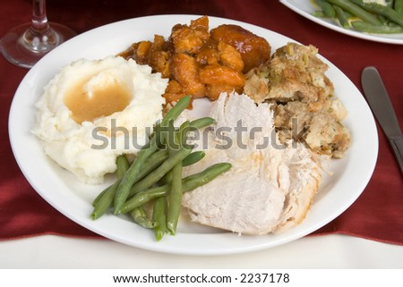 A plate of sliced turkey, stuffing, mashed potatoes and gravy, candied yams and fresh green beans. - stock photo