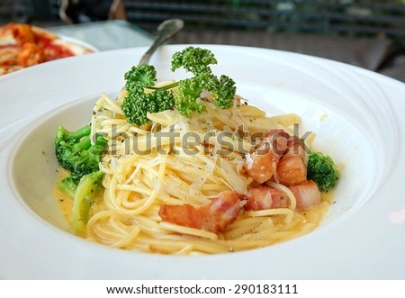 A plate of spaghetti Carbonara with broccoli and bacon and cheese. The image uses selective focus. - stock photo