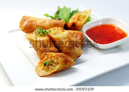 A plate of spring rolls with sweet chili dip sauce.
