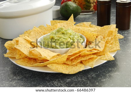 A plate of tortilla chips with organic guacamole - stock photo