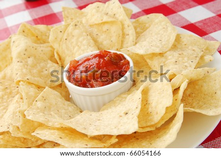 A plate of tortilla chips with salsa on a checkered table cloth - stock photo