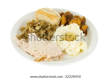 A plate of turkey, mashed potatoes and gravy, stuffing, sweet candied yams and a roll. - stock photo