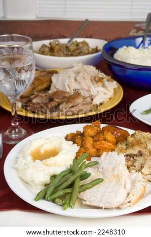 A plate of turkey, stuffing, mashed potatoes, gravy, green beans and candied yams sits on the dinner table. Other dishes can be seen in the background: plate of turkey, stuffing and mashed potatoes. - stock photo