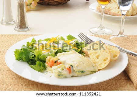 A plate of vegetable lasagna with salad and wine - stock photo