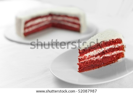 A plate with a slice of rich red velvet cake with cream cheese filling and coconut icing - stock photo