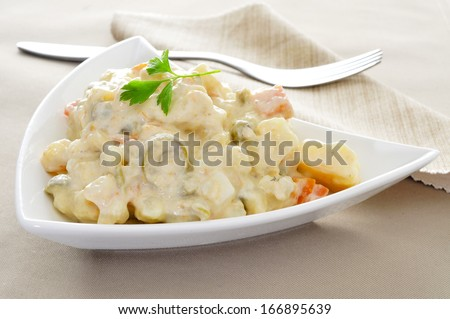 a plate with a typical spanish ensaladilla rusa, russian salad, on a set table