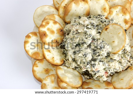 A plate with artichoke and cheese dip with pita bread chips.  - stock photo