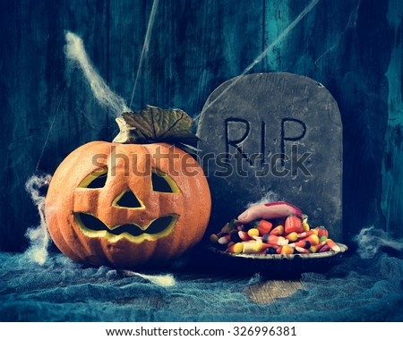 a plate with Halloween candies and an amputated finger in a dismal scene with a carved pumpkin and a gravestone with the text RIP carved in - stock photo