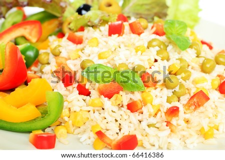 A plate with steamed long rice with green peas, corn and pepper. Isolated over white background. - stock photo