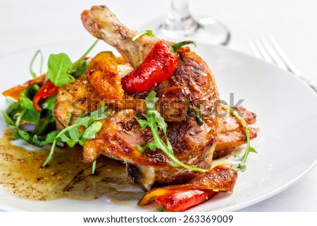 A plated meal of chicken with chili peppers - stock photo