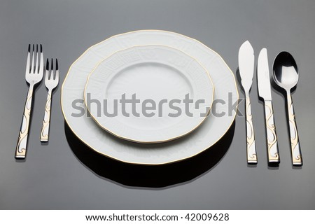A plates and a set of silverware on grey glass table - stock photo