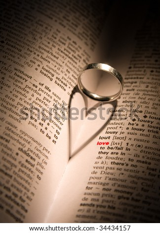 A platinum ring casts a heart-shaped shadow in a book with the word 'love' highlighted in red - stock photo