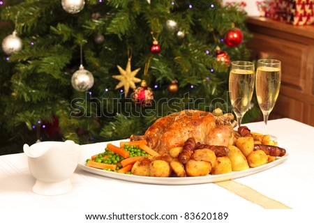 A platter containing a christmas dinner with a christmas tree in the background