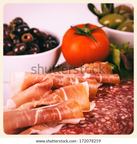 A platter of cold meats, olives, tomato, in a tapas style assortment. Cross-processed to look like an aged instant photo. - stock photo