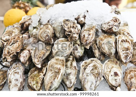 A platter of fresh raw oysters on ice at an outdoor cafe. - stock photo