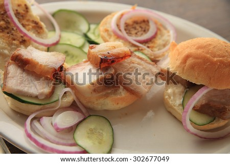 A platter of roast pork belly, cucumbers, onions and small rolls spread with whole grain mustard - stock photo