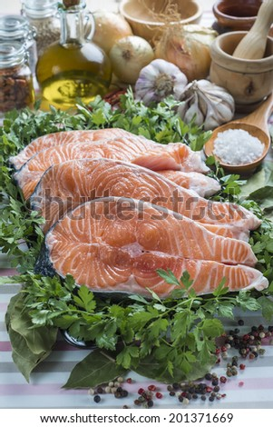 A platter with sliced fresh salmon and ingredients to cook it on the table of the kitchen - stock photo