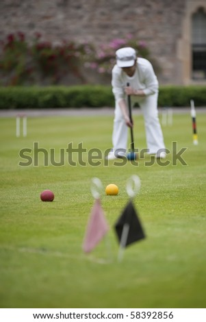 A player concentrating on a strike during game of croquet - stock photo