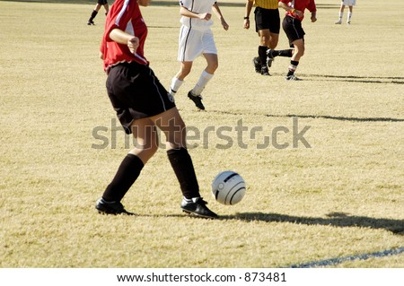 A player controls the ball in a girl's soccer game. - stock photo