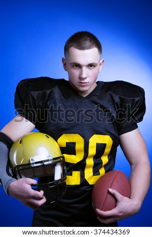 A player in american football holding ball and helmet. - stock photo