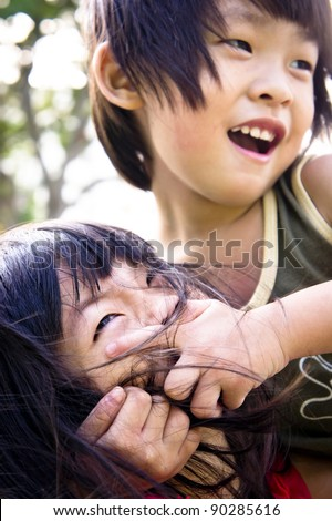 A playful Asian boy covering his sister's mouth not allow her to speak. - stock photo