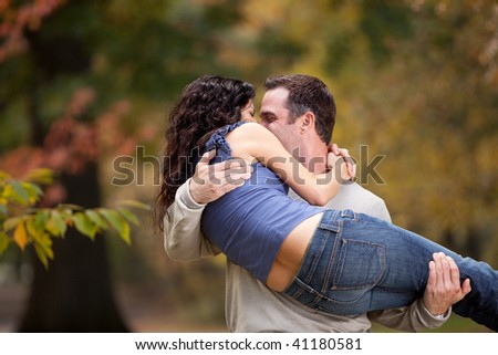 A playful couple - man holding woman in the park - stock photo