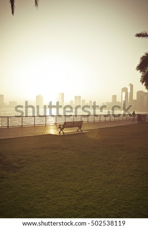 A pleasant morning on the corniche side. View of a city and a bench in the park.