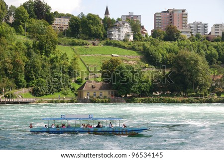 A pleasure boat carries tourists on the Upper Rhine the town of Neuhausen in northern Switzerland. It is sailing past the beautiful riverside. - stock photo