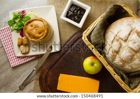 A ploughmans lunch spread out on burlap, bread board and distressed boards. Melton Mowbray pork pie with artisan boule bread in basket, by red Leicester cheese, butter, salad, pickle,and an apple.