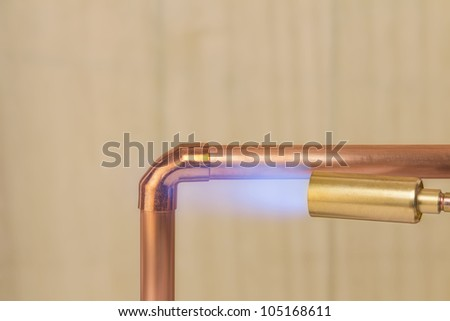 A plumbers hot gas soldering burner heating a copper elbow fitting to join two copper water pipes - stock photo