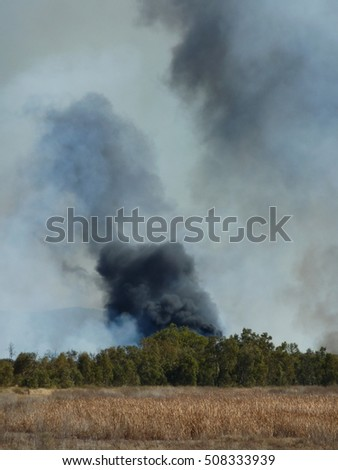 A plume of black and grey smoke ascends from the horizon above a bush fire in Australia's desert outback.