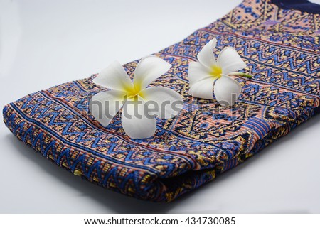 A plumeria and a purple towel isolated on the white background. Thai silk, Thai spa, Tropical spa - stock photo
