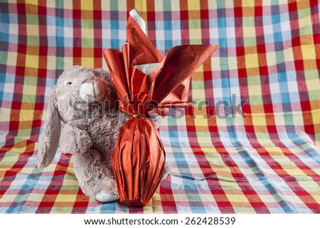 A plush bunny holding a brazilian Easters egg, on a colored background - stock photo
