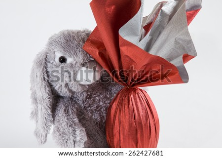 A plush rabbit holding a brazilian Easters egg, on a white background. - stock photo