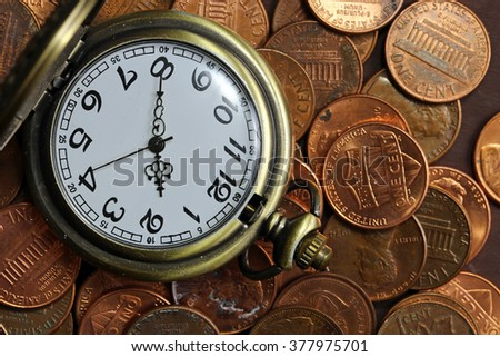 A pocket watch on a pile of pennies
