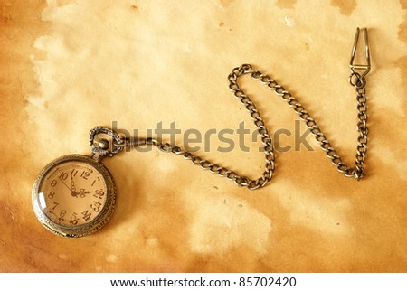 A pocket watch with a chain on a brown background. - stock photo