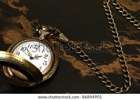 A pocket watch with a chain on a marble background. - stock photo