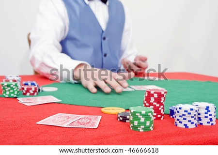 A poker game in progress with a dealer handing out cards - stock photo