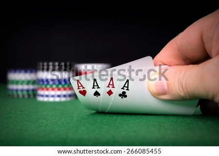 A poker hand of four aces with chips and copy space background for your text - stock photo