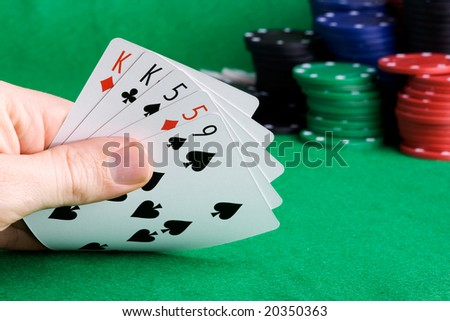 A poker hand with two pair and chips in the background