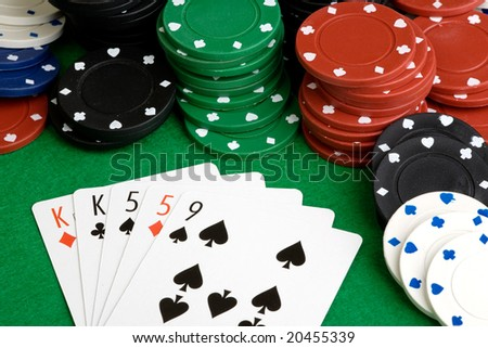 A poker hand with two pair on a green felt table